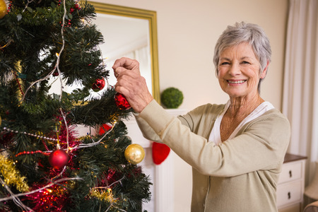 home decorating: Senior woman decorating the christmas tree at home in the living room Stock Photo