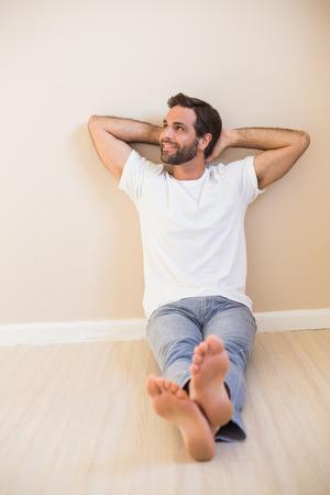 descansando: Feliz el hombre sentado en el suelo en su nuevo hogar