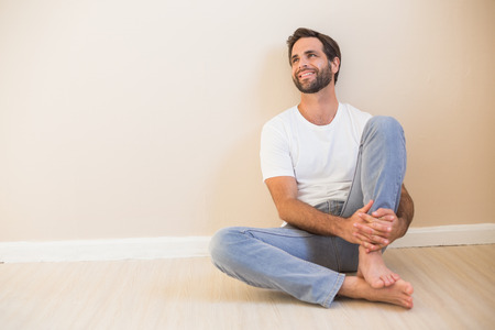 mid adult men: Happy man sitting on floor in his new home Stock Photo