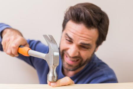 Casual hombre martillando su dedo por accidente en su casa en la sala de estar Foto de archivo