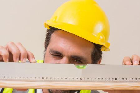 Bauarbeiter mit Wasserwaage in einem neuen Haus Standard-Bild