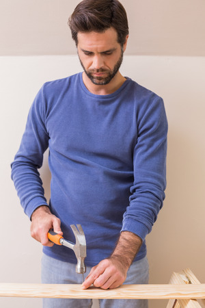 hammering: Casual man hammering nail in plank at home in the living room