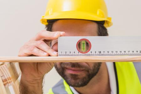 albañil: Trabajador de la construcción mediante nivel de burbuja en una casa nueva