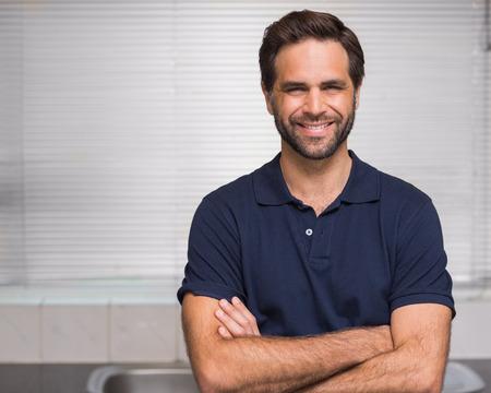 Casual hombre sonriendo a la cámara en casa en la cocina