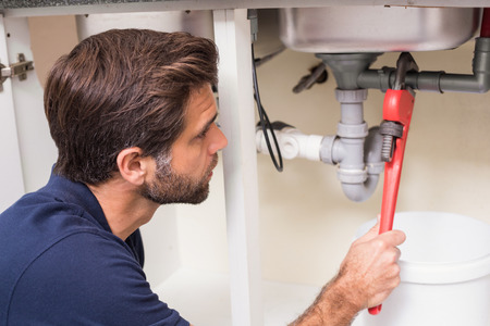 plumber: Fontanero fijación de debajo del fregadero en la cocina Foto de archivo