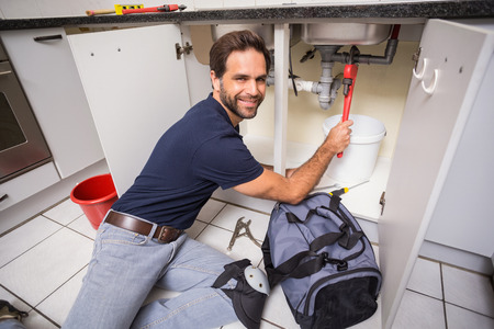 Plumber fixing under the sink in the kitchen photo