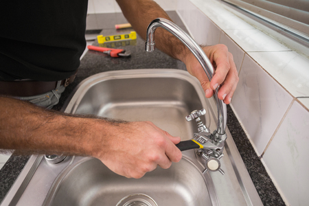 plumbing tools: Plumber fixing the sink with wrench in the kitchen Stock Photo