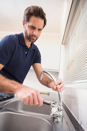 Plumber fixing the sink with wrench in the kitchen photo