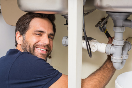 plumber: Happy plumber fixing under the sink in the kitchen