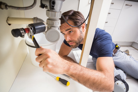 repair man: Plumber fixing under the sink in the kitchen