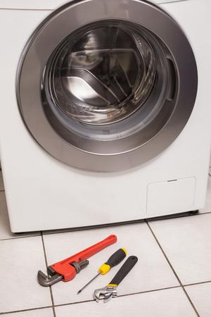 lavadora con ropa: Lavadora con herramientas en la cocina Foto de archivo