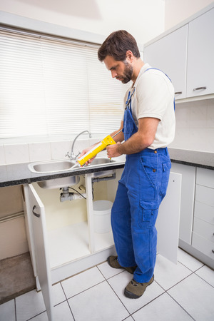 Plumber putting filling in between tiles in the kitchen Stock Photo