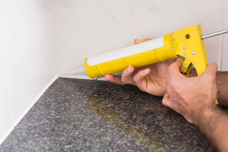 stone worktop: Plumber putting filling in between tiles in the kitchen Stock Photo