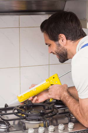 site preparation: Plumber putting filling in between tiles in the kitchen Stock Photo