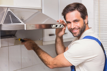 construction worker: Handyman fixing the oven in the kitchen