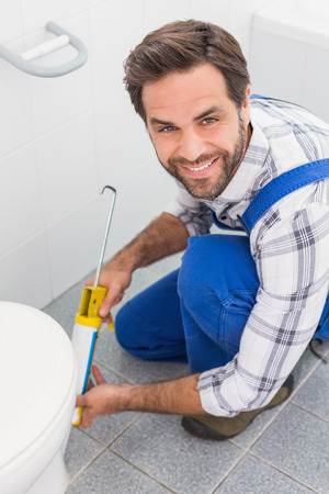 Handyman filling in tiles in bathroom in a new house photo