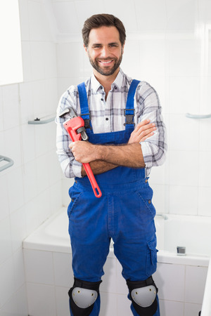 professional portrait: Plumber smiling at the camera in the bathroom Stock Photo