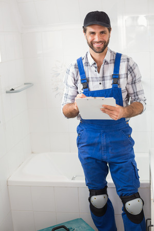 Plumber taking notes on clipboard in the bathroom photo