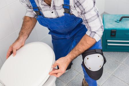 fontanero: Fontanero que instala la tapa en el inodoro en el baño Foto de archivo