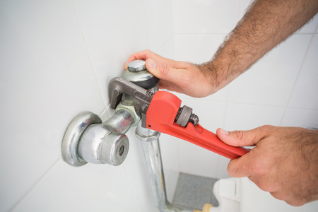 plumber: Plumber fixing tap with wrench in the bathroom Stock Photo