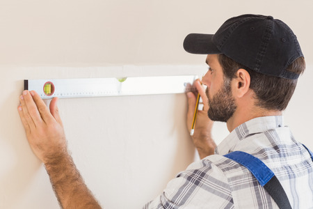 Construction worker using spirit level in a new house photo