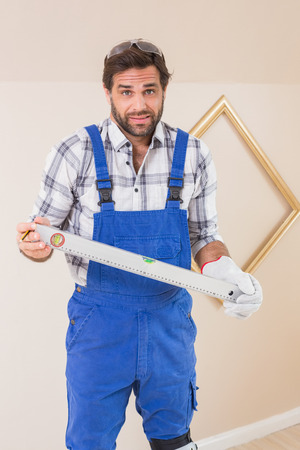 wonky: Confused construction worker holding spirit level in a new house