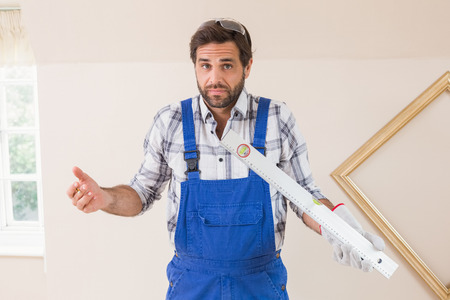 Confused construction worker holding spirit level in a new house photo