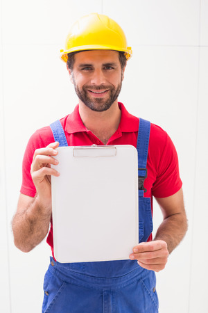 worker construction: Construction worker showing clipboard to camera in a new house Stock Photo