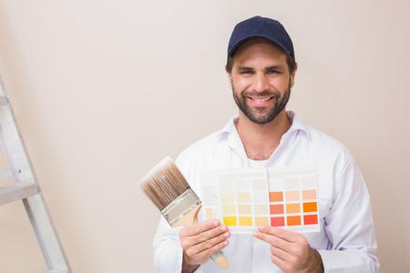 pintor de casas: Pintor que sostiene una carta de colores sonriendo a la c�mara en una casa nueva Foto de archivo