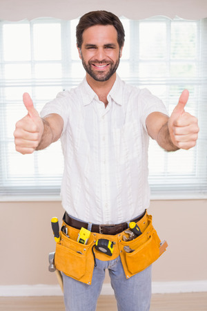 Handyman smiling at camera in tool belt in a new house Stock Photo