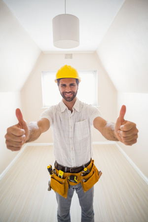 thumbsup: Handyman smiling at camera in tool belt in a new house Stock Photo