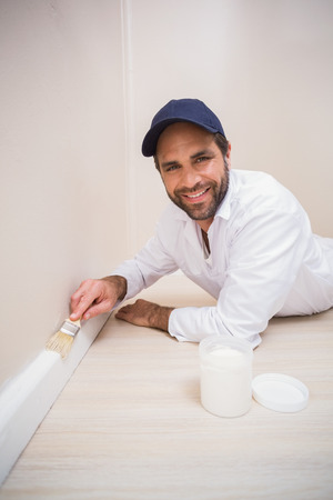 skirting: Painter painting the skirting boards in a new house