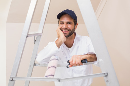 house painter: Painter smiling at the camera in a new house Stock Photo