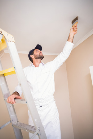 house painter: Painter standing on ladder painting roof in a new house