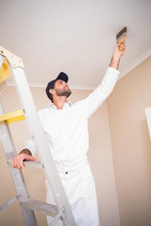 pintor de casas: Pintor que se coloca en el techo de la pintura de escalera en una casa nueva