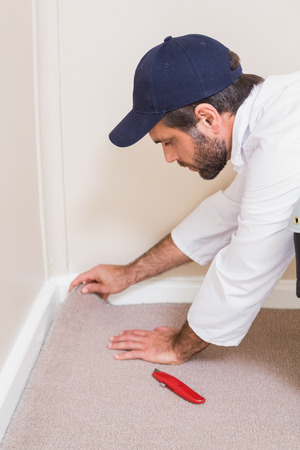 tucker: Handyman laying down a carpet in a new house