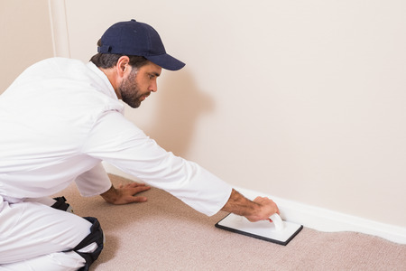underlay: Handyman laying down a carpet in a new house