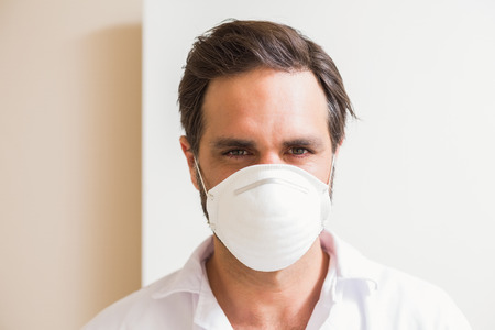 protective mask: Carpenter wearing protective mask looking at camera in a new house Stock Photo