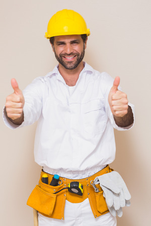 Handyman showing thumbs up to camera in a new house photo