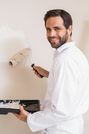 house painter: Painter painting the walls white in a new house Stock Photo