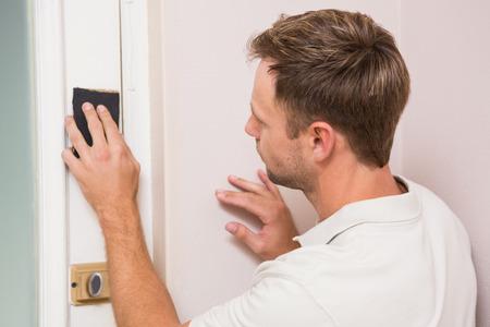 sanding block: Man hand sanding the door before refinishing at home