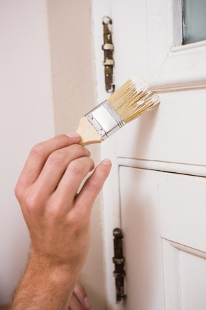 Painter painting the door white in a new house photo