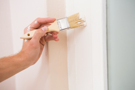 house painter: Painter painting the door white in a new house