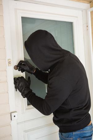 intruding: Burglar breaking open the door of someones home Stock Photo