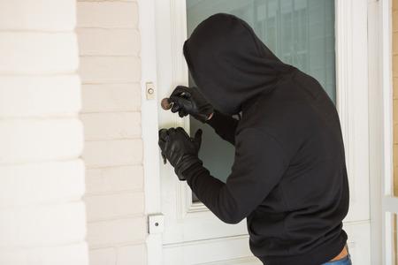 Burglar breaking open the door of someones home 版權商用圖片