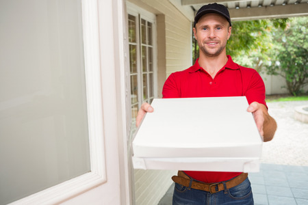 delivery man: Pizza delivery man delivering pizzas to a house