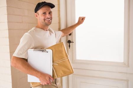 knocking: Smiling handyman knocking at the door of someones home