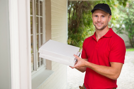 pizza delivery: Pizza delivery man delivering pizzas to a house