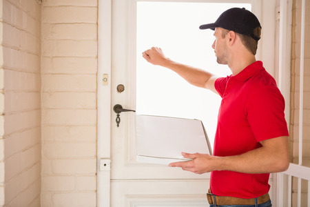 door man: Delivery man holding pizza while knocking on the door to a house