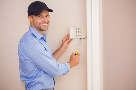 Smiling handyman fixing an alarm system on the wall Stock Photo
